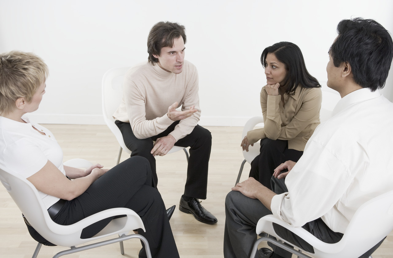 four people in circle sitting down and talking