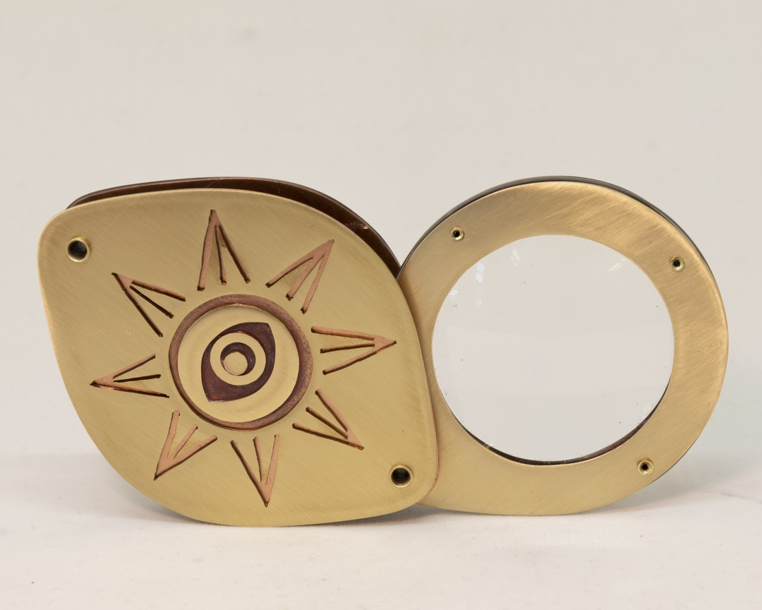 close of brass ring with sun pattern