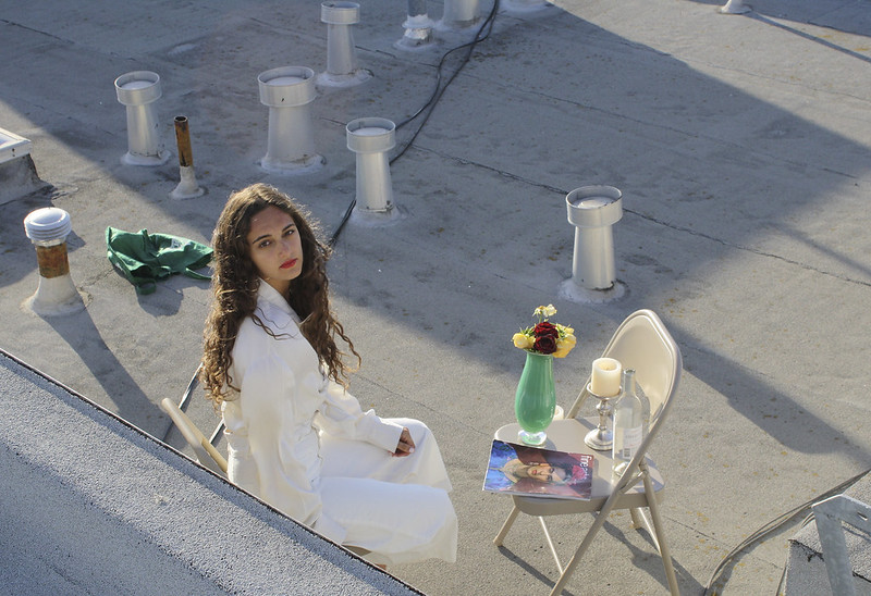 young woman in a white dress on a rooftop