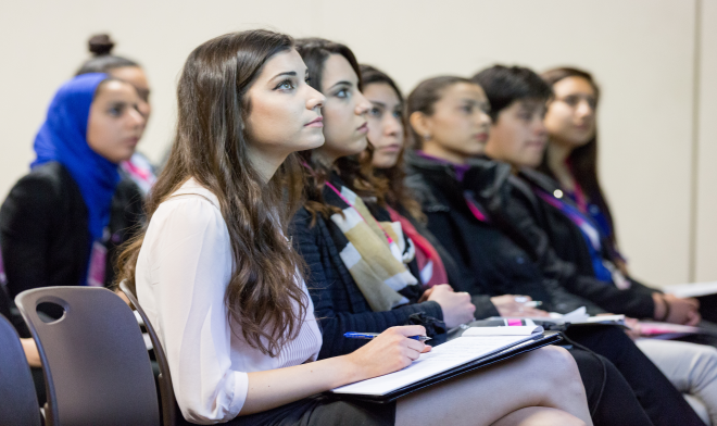 Image of a group of attentive students at the women in engineering conference.